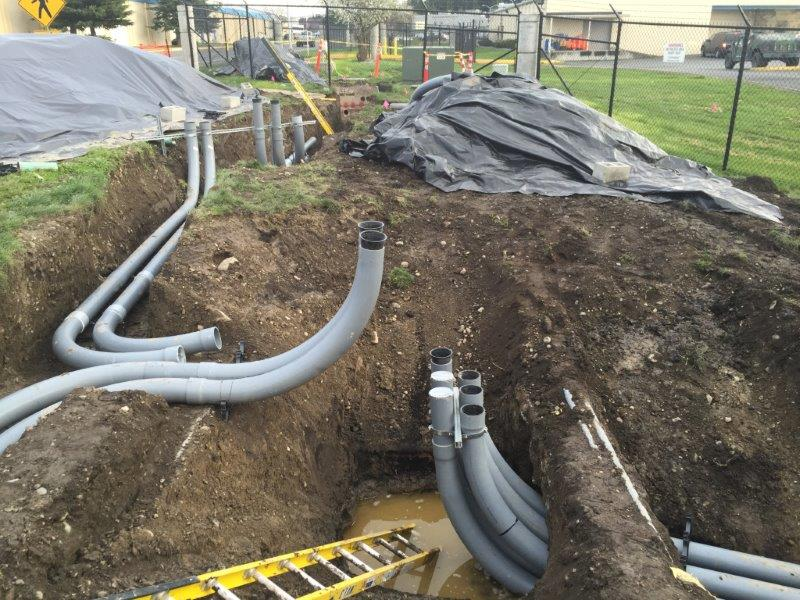 Five inch PVC conduit is installed underground. Upon completion it will contain 12,470 volt conductors to serve two transformers serving the simulator building.